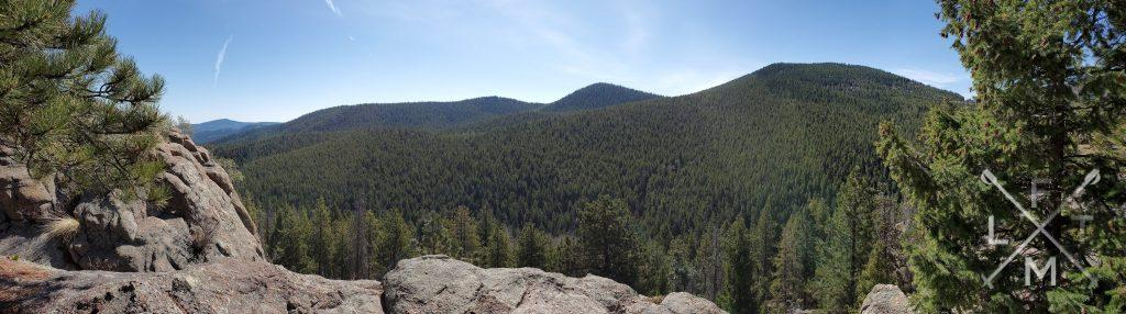 Panoramic picture.  The picture is lined on either edge by trees with a rock ledge in the fore ground framing the view like a picture window.  The view is of 3 hills and valley that are entirely covered in trees with the suns rays shinning down on the hills.