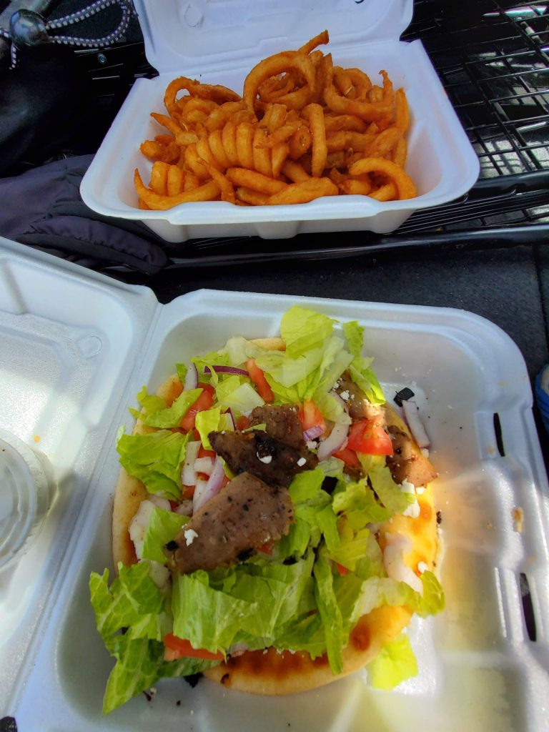 A plate of curly fries and a gyro with fresh vegetables and gyro meat from the Country Road cafe in Evergreen