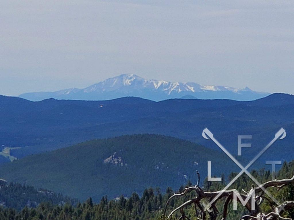 A view from the trail on Bergen peak.  Three distinct levels of hills are visible.  In the foreground a tree covered small hill, in the midground the foothills also tree filled and green in color. In the background snow capped mountain of the rockies.