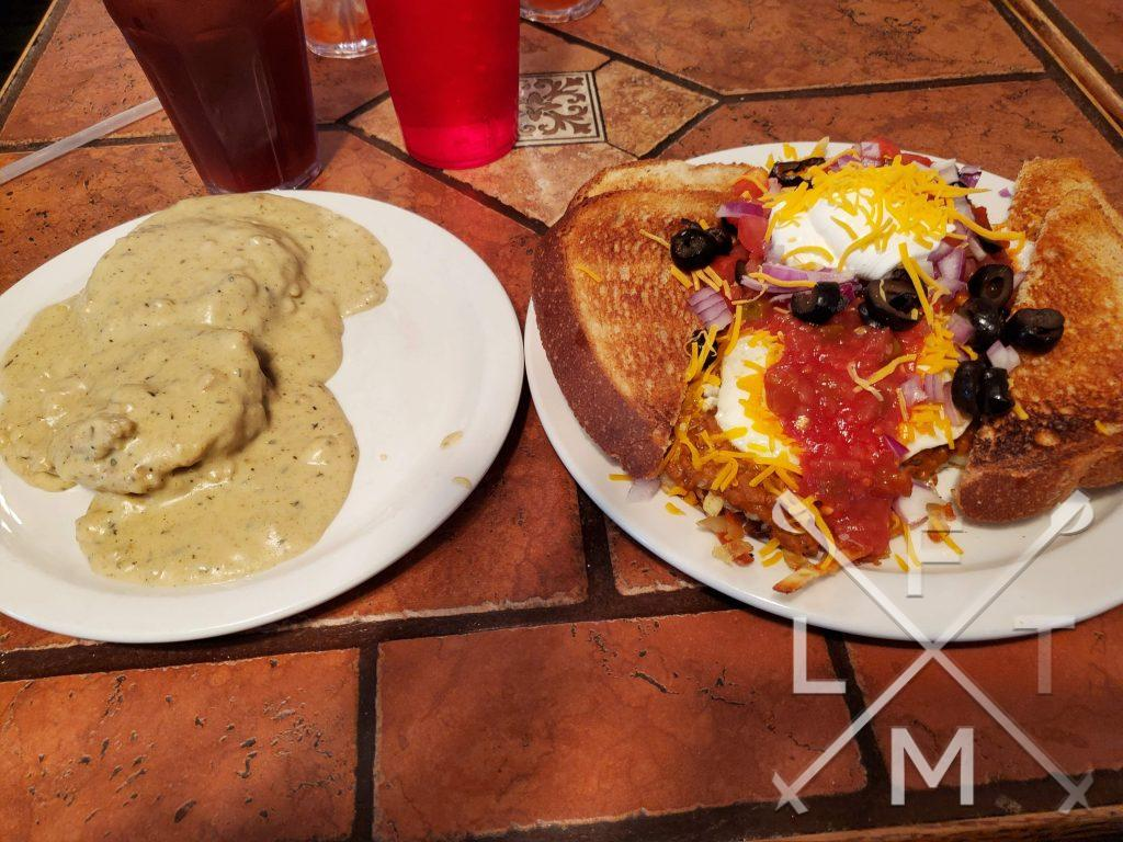 a very large spread. On the left plate biscuits and gravy.  On the right plate, split toast on either edge. In the middle the Broken arrow ranch eggs. Eggs with taco meat, black olives, onions, cheese salsa and sour cream. Served by Cheyenne Crossing restaurant