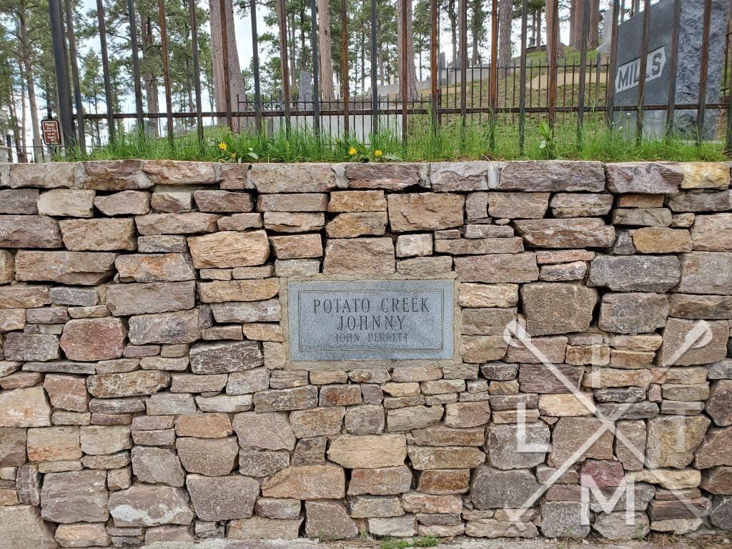 A brick retaining wall supporting the gravesite has an engraved rock marker showing that above the hill lies Potato Creek Johnny