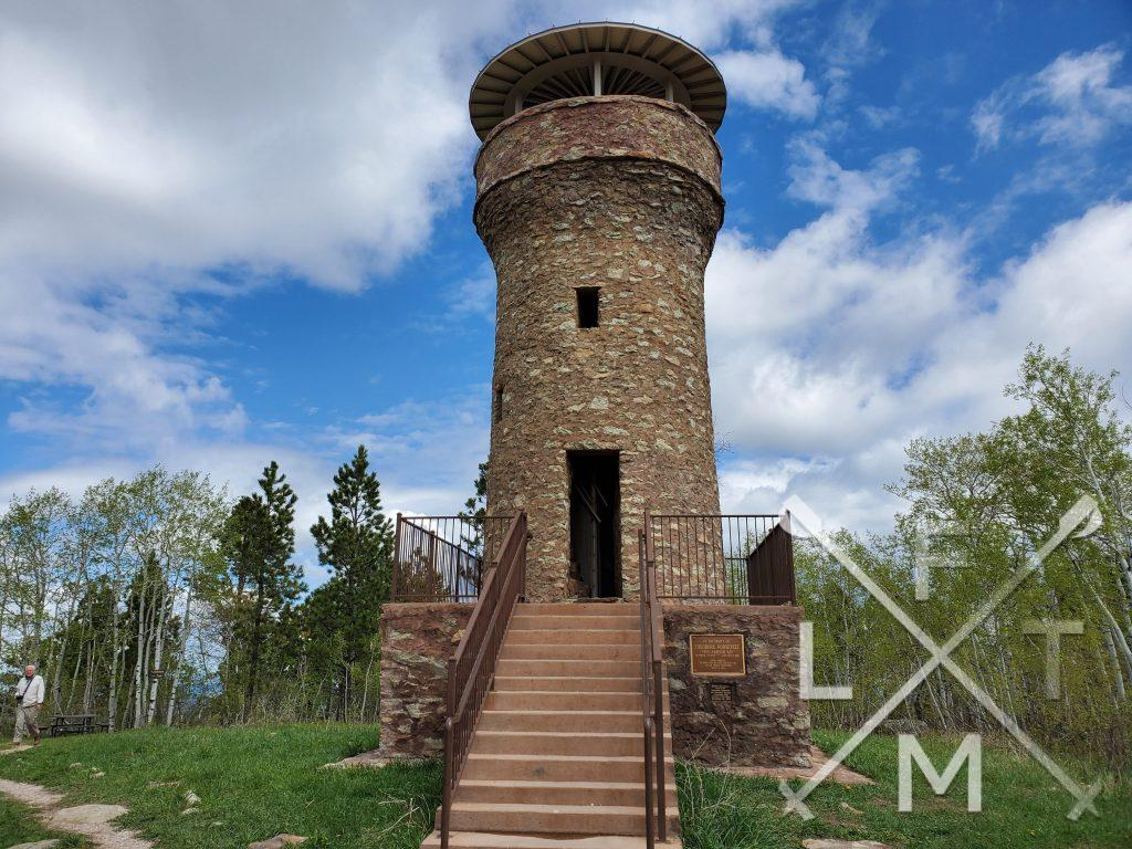A wide view of the Friendship tower.  The tower is made completely of brick and in a cylindrical shape.  There is an open doorway, an open window and an open observation area at the top.