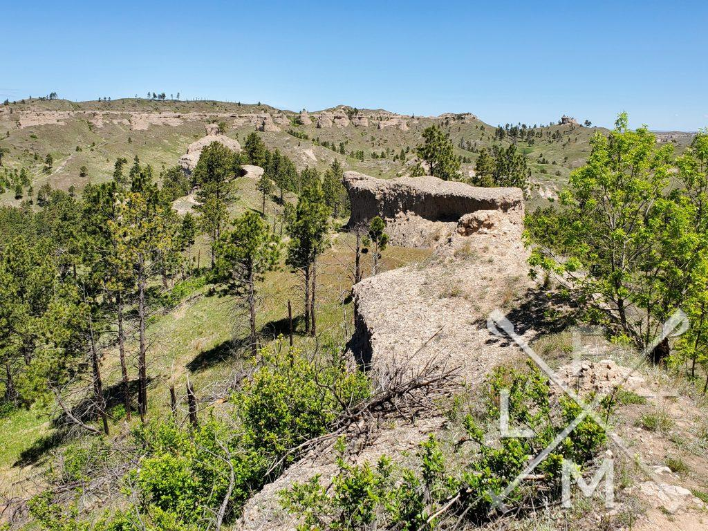 From the top of the trail there is a panoramic view of the entire park.  A rocky wall stretches ahead like a snake across the top of the hill.  In the distance there are rocky high points with trees throughout.