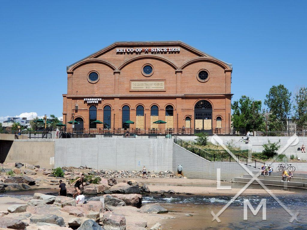 The exterior of the R.E.I. flagship store in Denver with the Platte river and confluence park in the foreground
