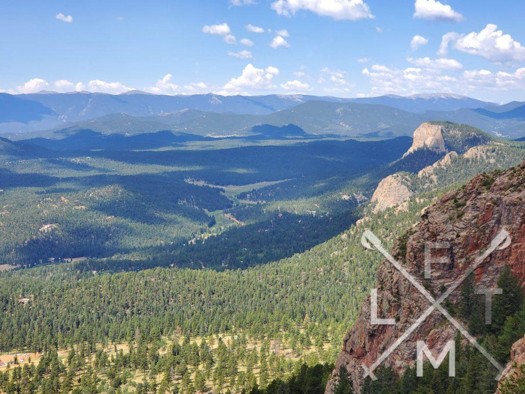 The view from Pikes Peak overlook.  Lions Head is more prominant and the valley below is lush with trees.  Shadow's from the clouds dot the landscape.