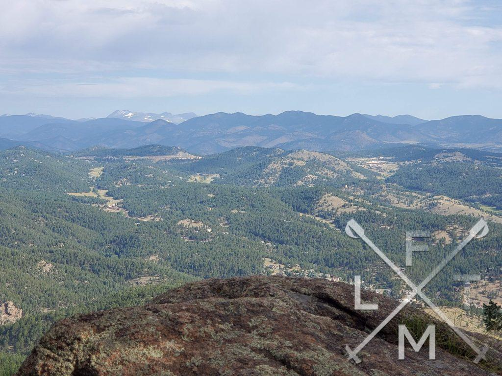 The view from the top of independence peak.  There is tree covered foothills in the foreground leading up to snow covered mountains in the background.