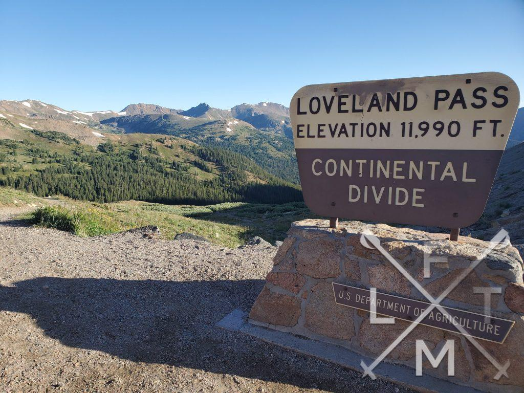 The view from the top of Loveland Peak and the sign for the continental divide in the foreground.