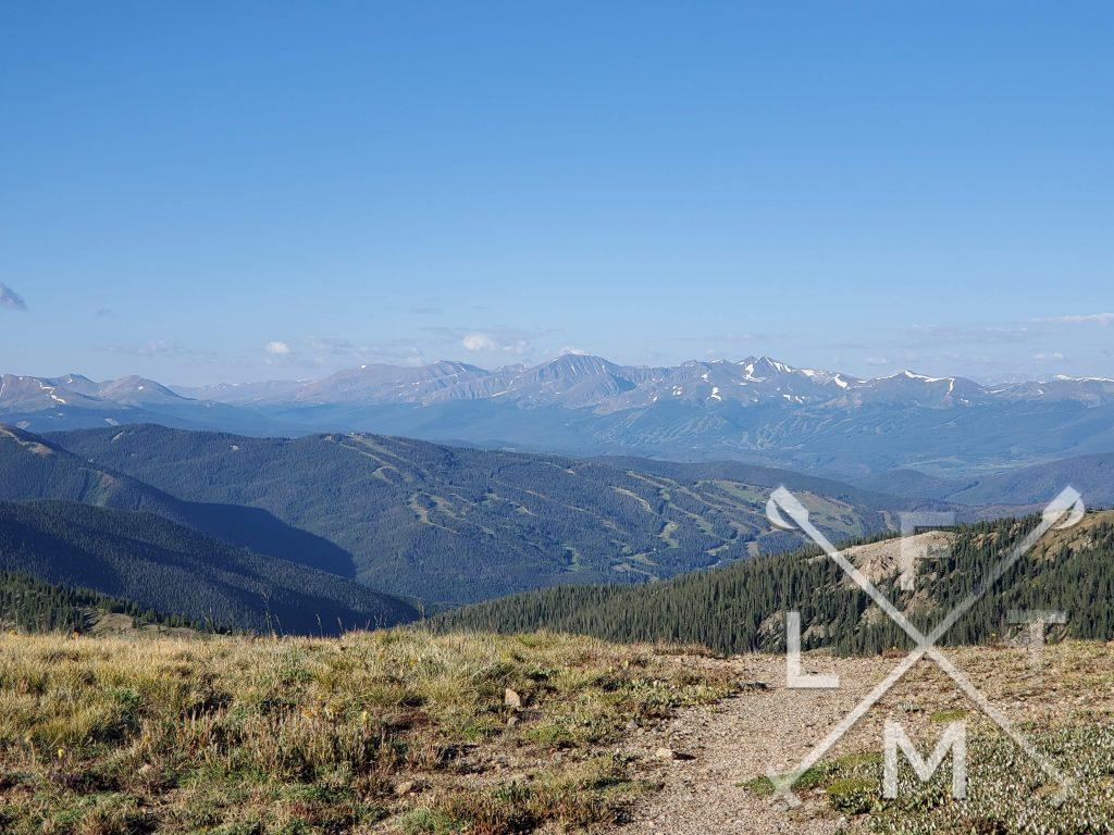 The view from the second hill on the trail to Rotary Peak.  Snow capped mountains in the background with a large valley in the foreground.