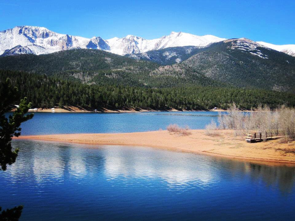 Pikes peak with a lake and sandbar in the foreground and snow capped mountains in the background.