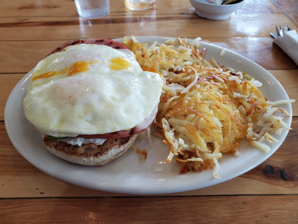 Ned's famous Muffin.  An English muffin with two fried eggs on top of fried ham, cream cheese, and avocado with a side of hash browns.
