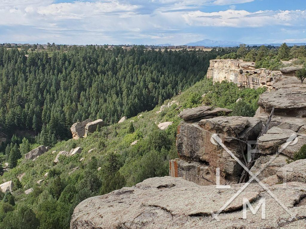 The view near the end of the hike.  On the right, a wall of rock towers above trees.  On the left, evergreen trees blanket the landscape.  Way in the distance pikes peak looms.