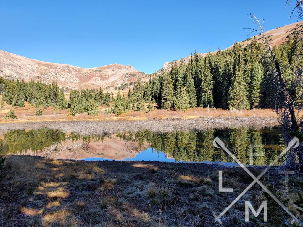 A pond with a reflection of mountains and pine trees.