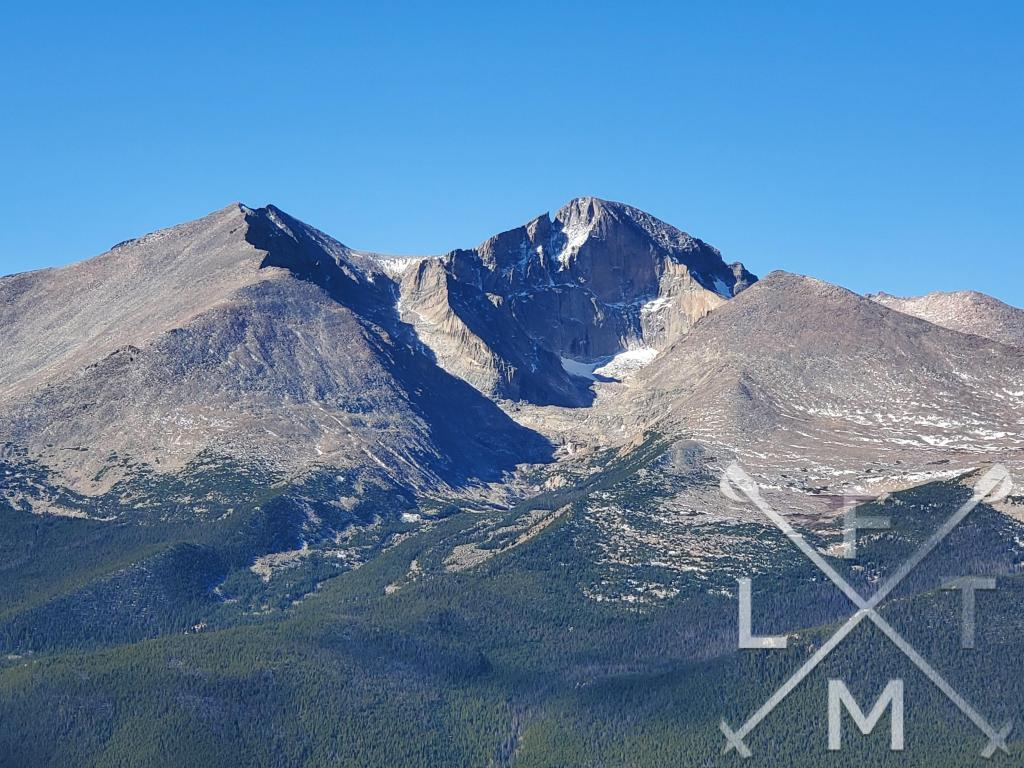 Longs Peak from the top of the West Sister.  A clear view the mountain with snow sporadically covering its face.