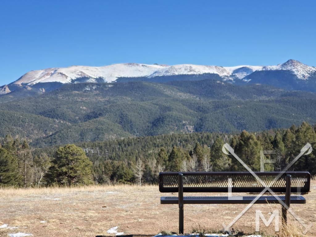 A bench in the foreground of a view of Pike's Peak stretching towards the sky in the background.