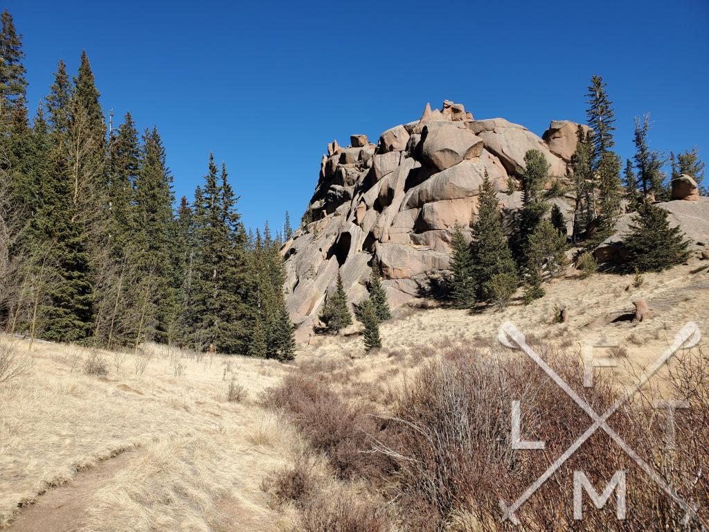 A large rock mound just off the trail that towers over the path.