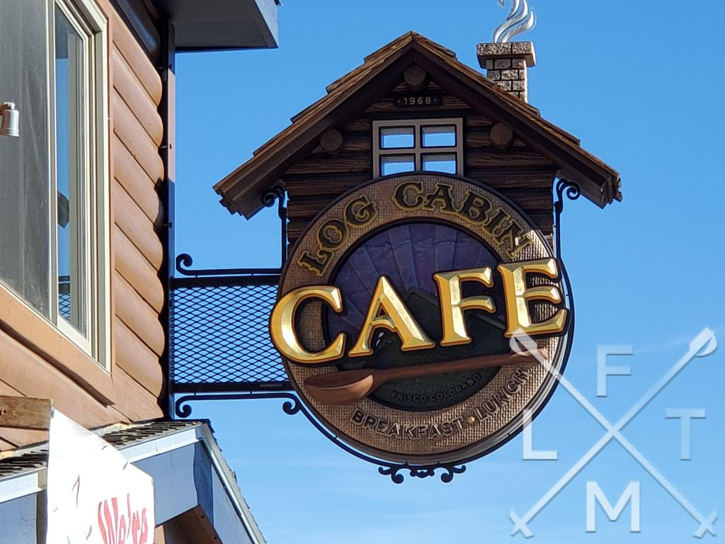 The sign for the Log Cabin Cafe.  A round side with a miniature log cabin above it.
