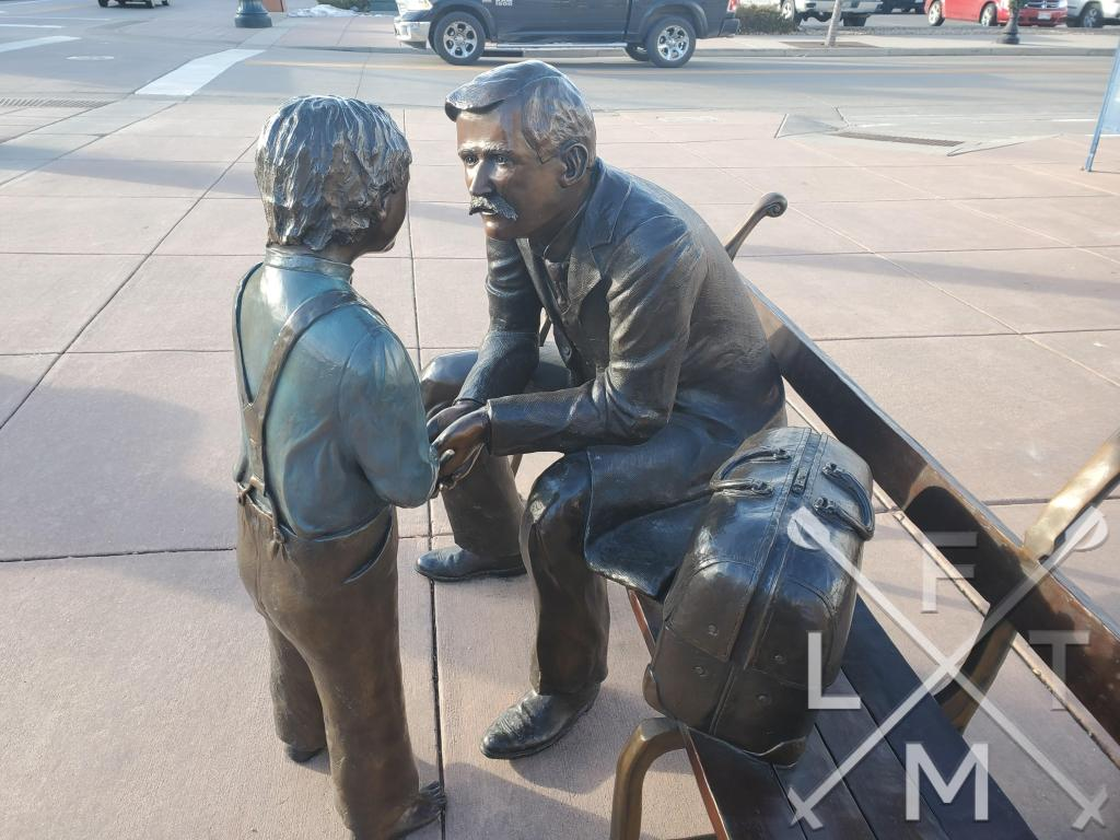 A bronze statue of one of the towns founding doctors  talking to small boy.