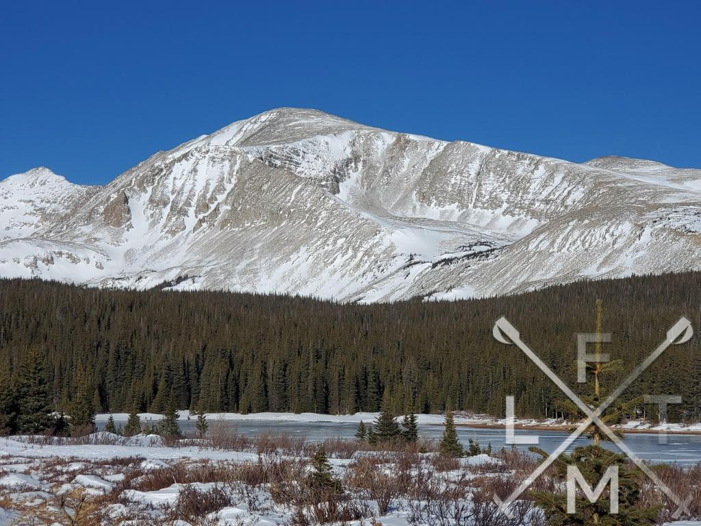 A snow covered mountain in the background towering over Brainard Lake.  The is the second lake on the Brainard Long Lake (Winter) Loop