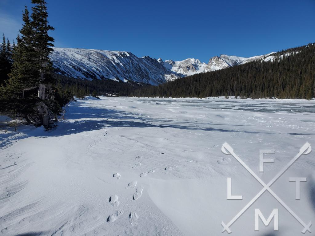 A frozen Long Lake ringed in the background by the Indian Peaks Range on the Brainard: Long Lake Loop (Winter) hike.