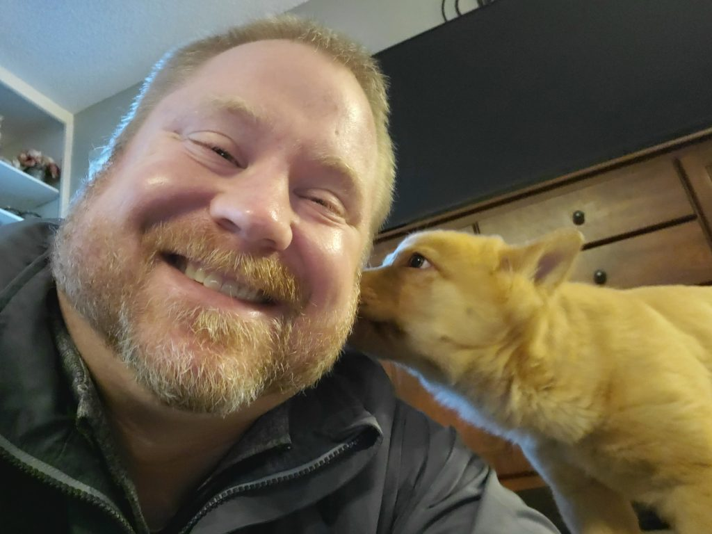 A picture of me and a puppy sniffing my ear.