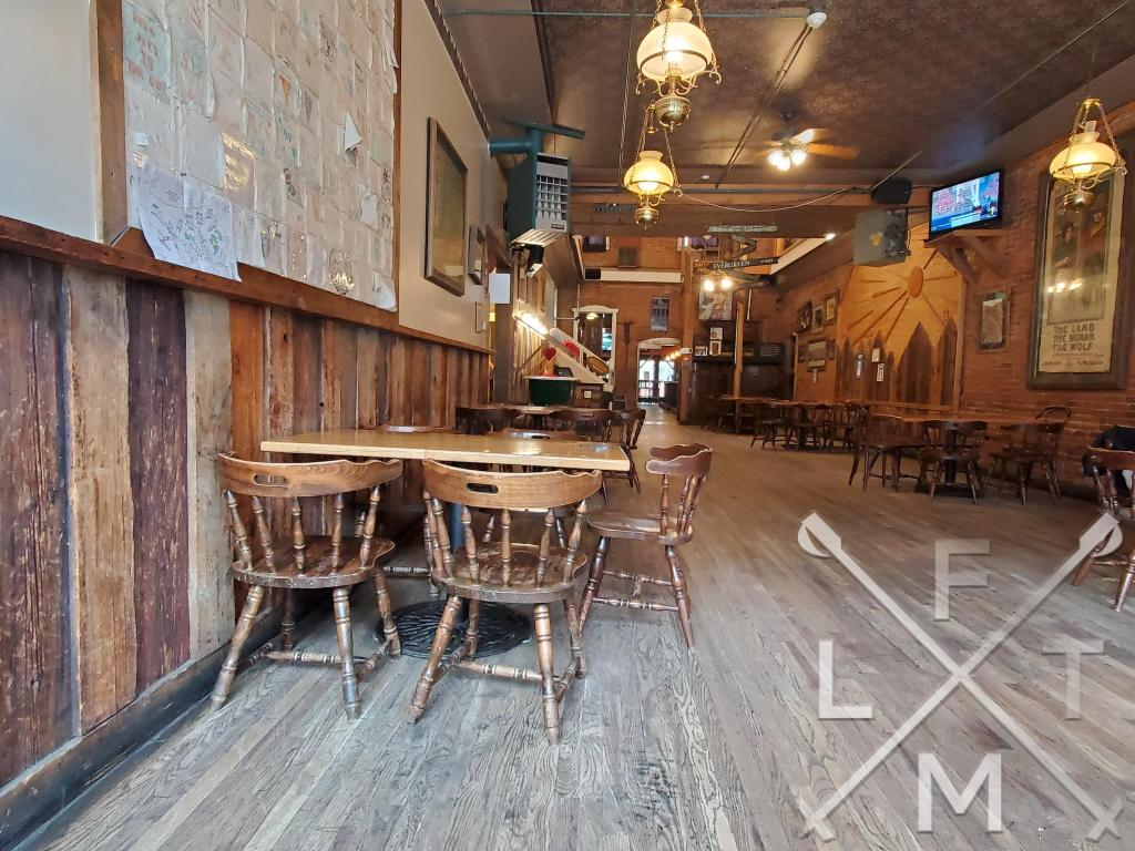The inside of the Beau Jo's with old wood paneling on the walls and an old wood floor.  It really feels like it is from the 1800's
