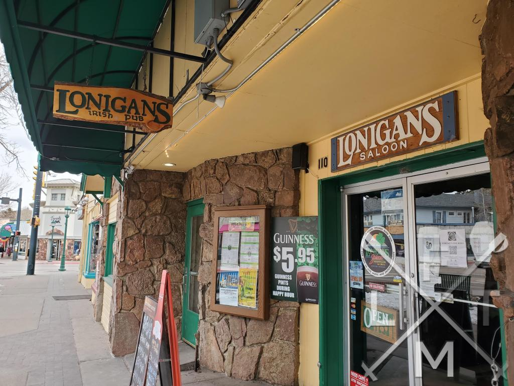 A wood sign hangs on the street and above the door in the front of Lonigans Irish Pub.