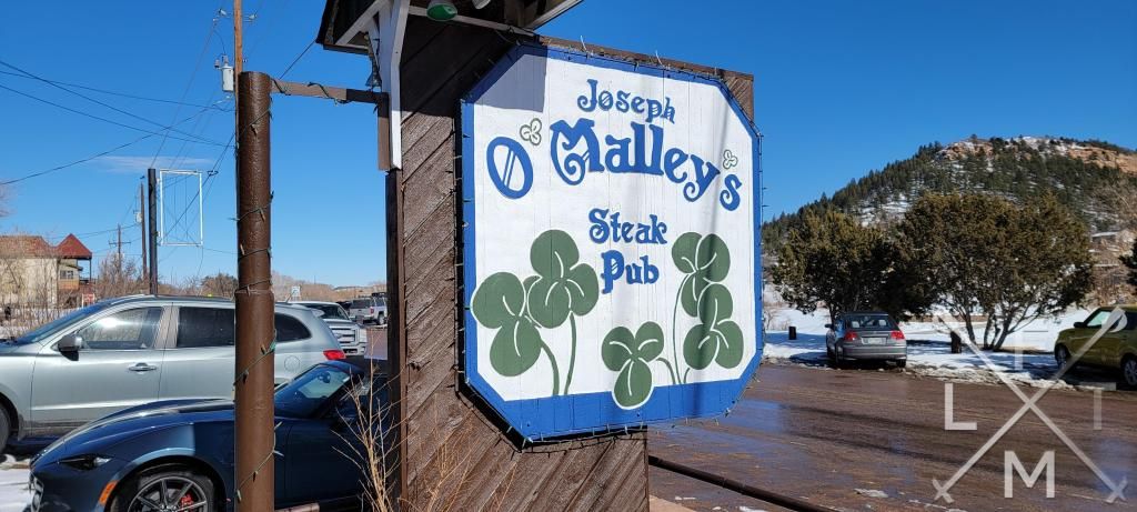 The sign for O'Malley's Steak Pub with green clovers in Palmer Lake Colorado.
