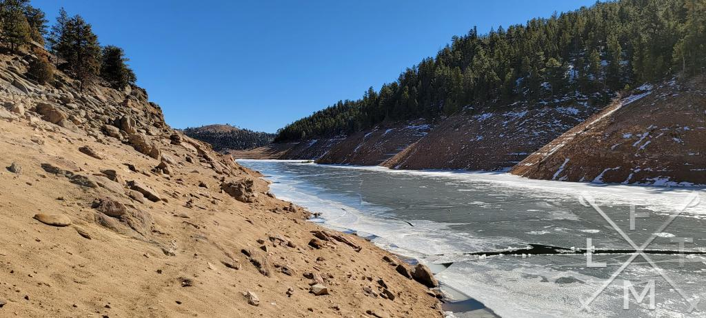The cove of Gross Reservoir from Forsythe Canyon.  There are sandy hills on either side of the frozen water.