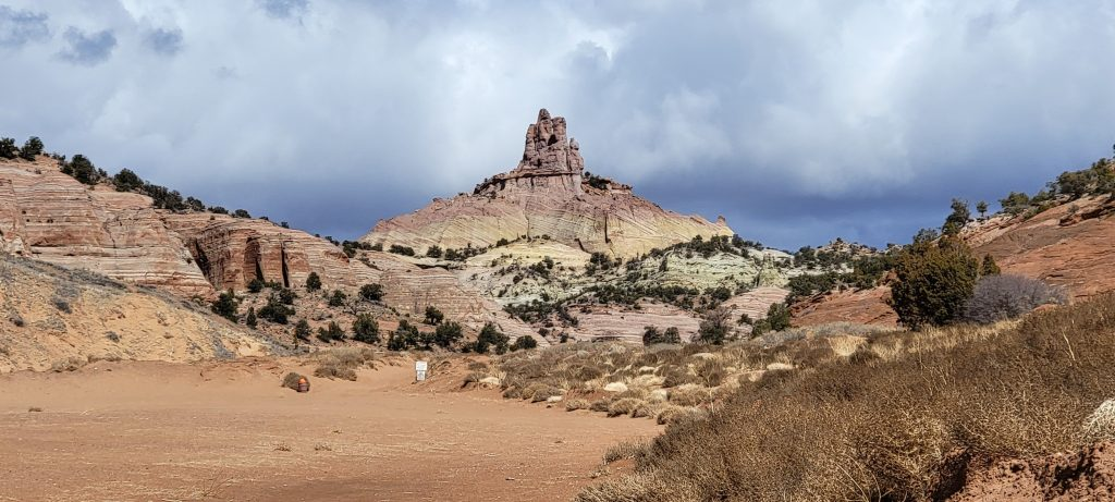 The Church Rock in the distance across a flat dirt field on the Church Rock Trail.