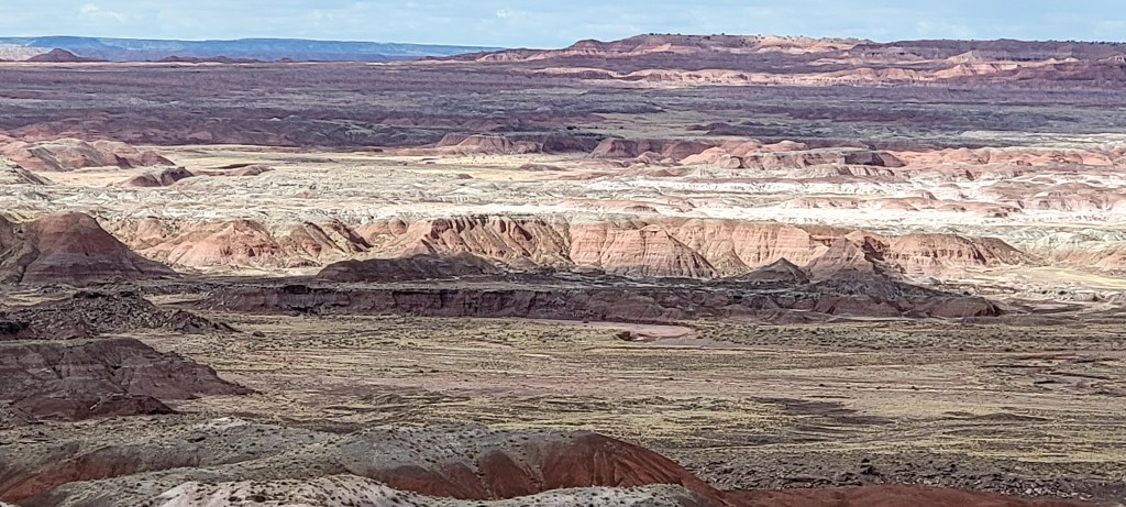 A wide shot from the top of the mesa shows how far the rock formations expand from the Painted Desert Rim Trail.