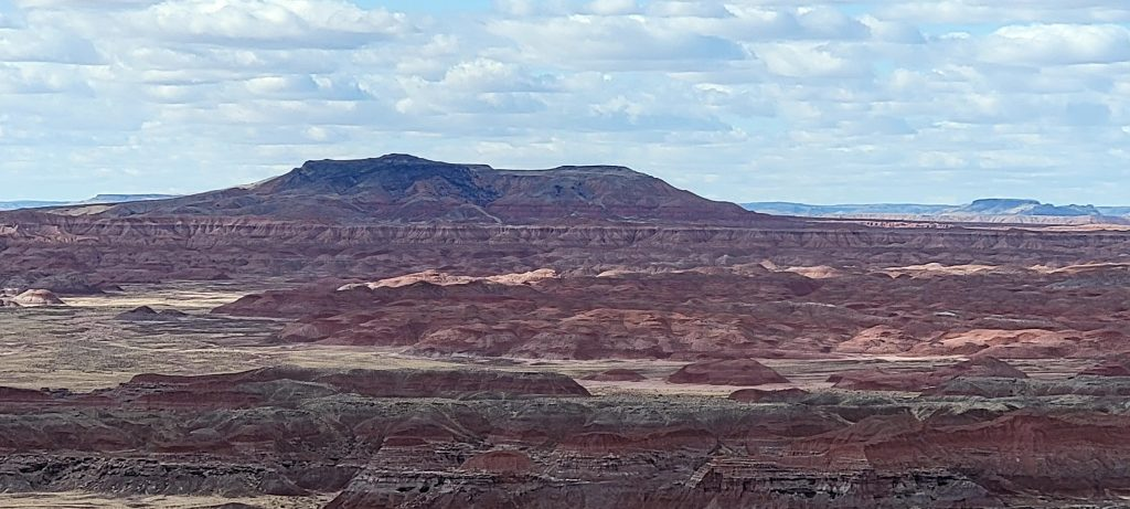 A wide shot from Kachina Point on the Painted Desert Rim Trail.  A large peak looms in the background and below that are red hills.