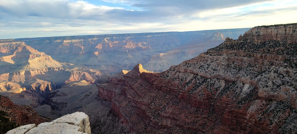 The sun has risen at the Grand Canyon.  The sky has turned blue with the floor of the canyon light or dark depending on if the sun is hitting an individual rock formation.