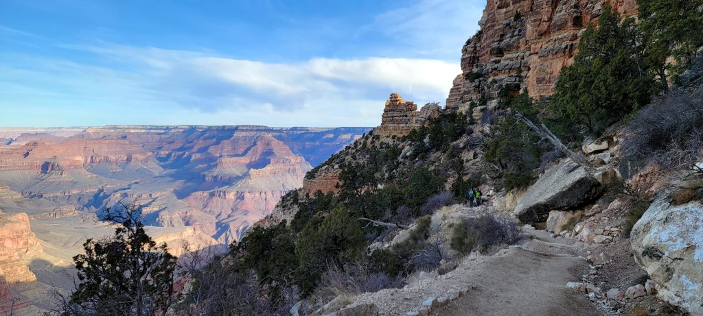 The trail to Ooh Aah Point in the foreground with a rock wall on one side and the open view into the canyon on the other.