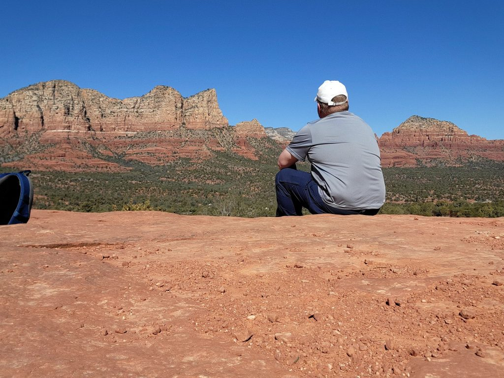 The Fatman sitting on a rock looking out over some beautiful red rock formations on the Yavapai Vista Trail