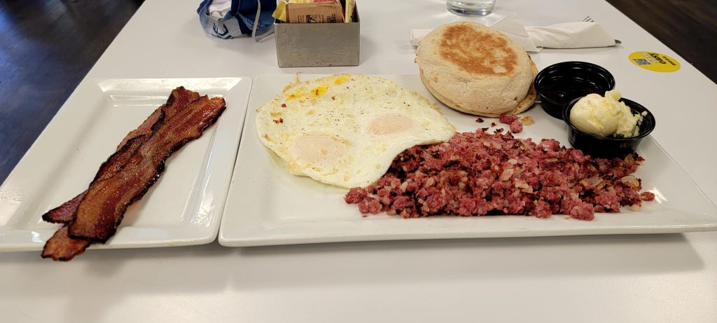 Corned Beef Hash with eggs cooked over easy.  An English Muffin and side of bacon.