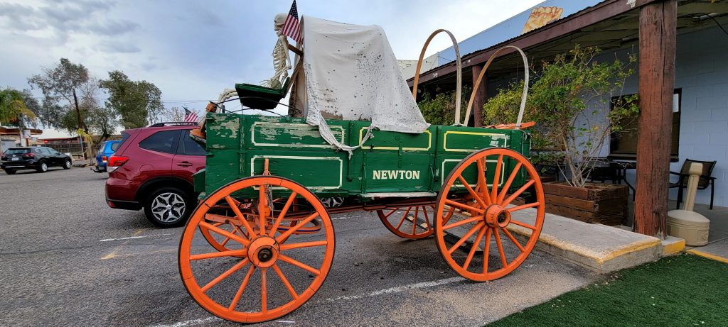 An old, partially restored wagon from the wagon train days sits in the parking lot of the Rock Springs Cafe.