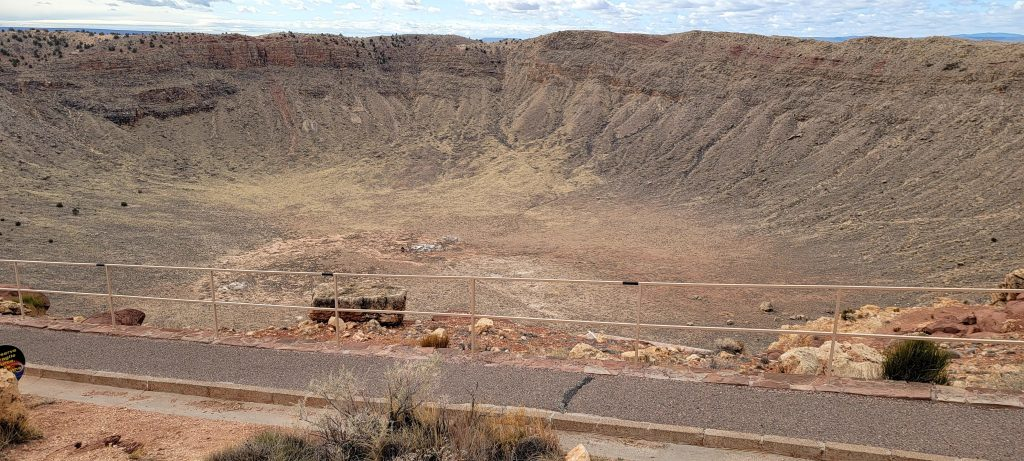 A concrete walkway in the foreground for reference with the meteor crater descending below the walk way.